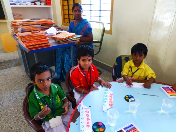 Decorating their hats...with their class teacher, Mrs Vijaya, in the background